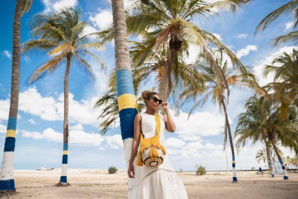 żółta plecioną torebka w stylu boho z pomponami
